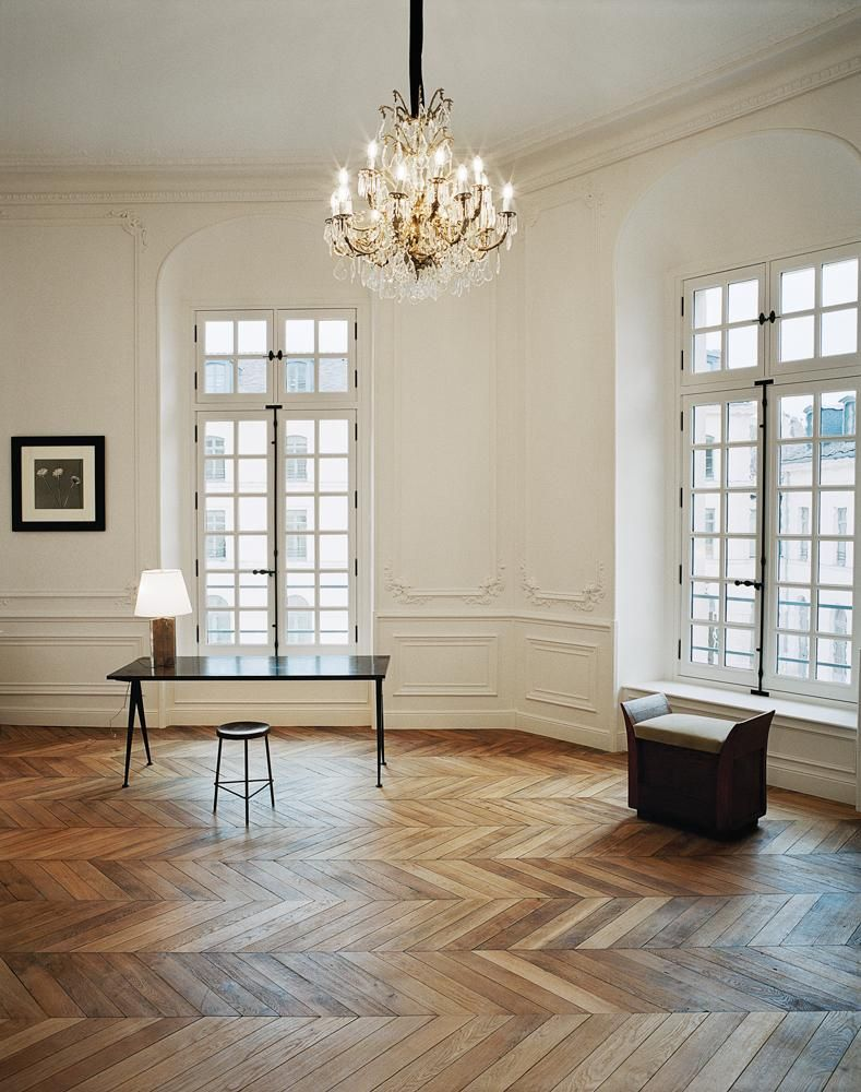 "A room featuring a Jean Prouvé table and a Pierre Jeanneret stool, next to a 1982 photograph by Robert Mapplethorpe. ""We wanted to leave behind [the former headquarters at] Avenue George V and position the Saint Laurent brand somewhere more elevated and chic,"" says Vaccarello."