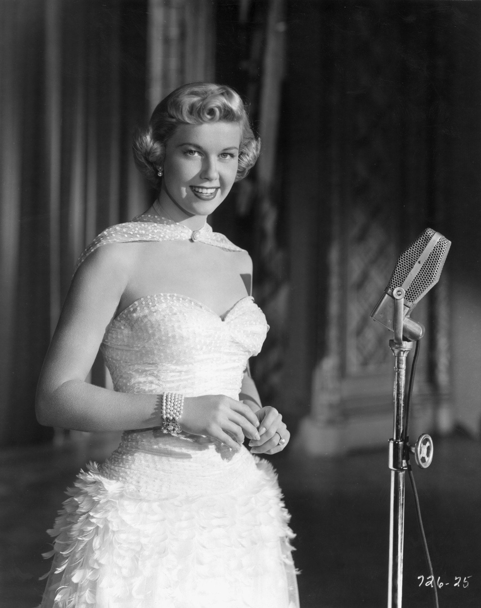 Doris Day smiling as she stands behind a microphone from director Michael Curtiz's film 'Young Man with a Horn'